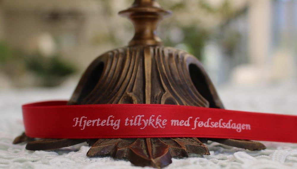 Bånd: Kardinal rødt. Tryk: hvidt. Skrift: Corsiva