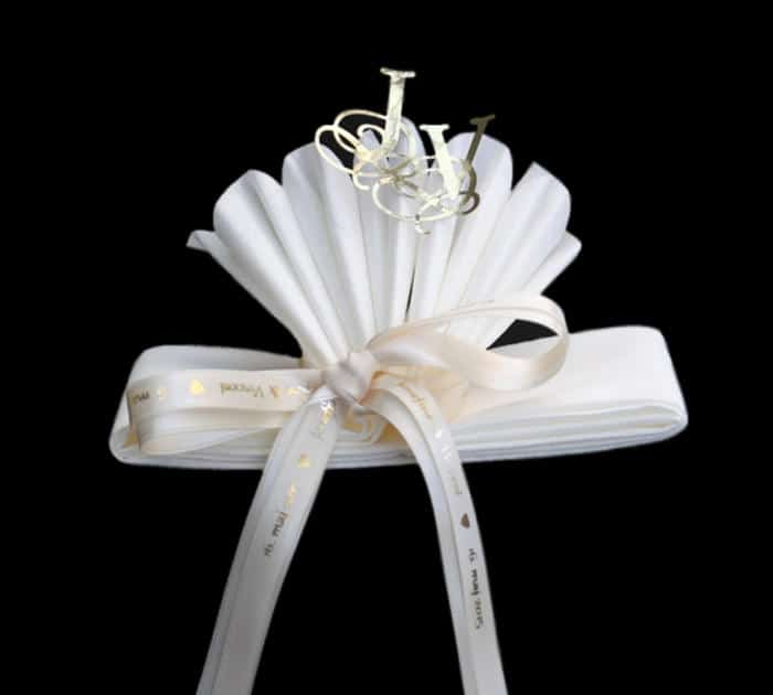 serviet foldet som vifte og bundet med silkebånd med påtrykt tekst
